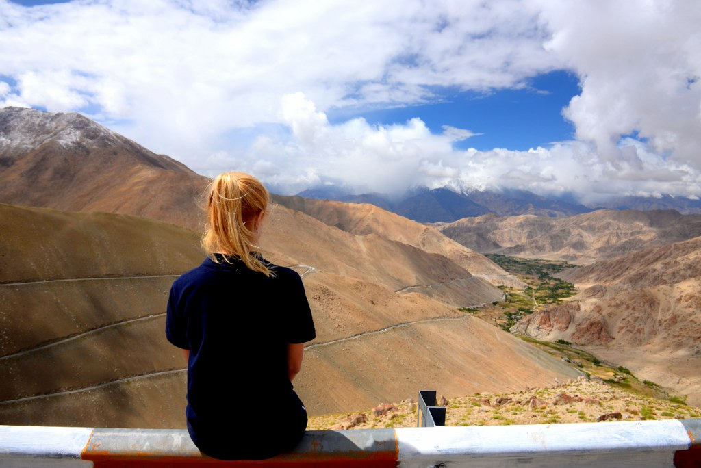 a_blonde_girl_sitting_on_a_mountain_edge_in_the_himalayas