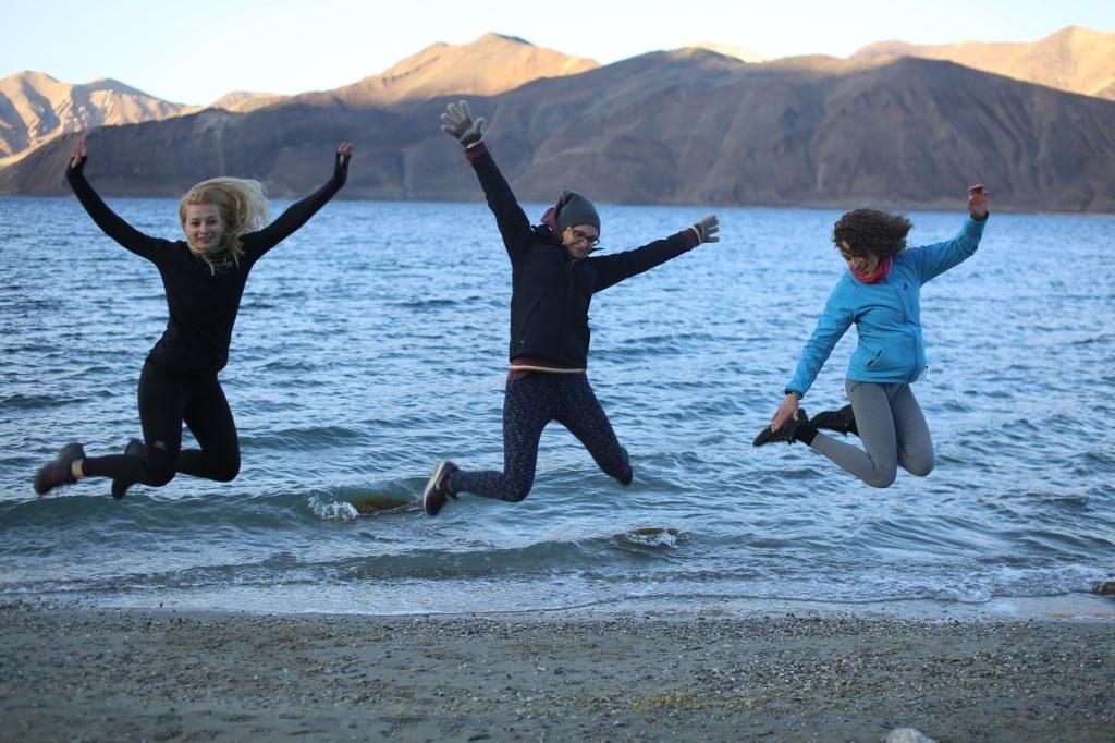 three_girls_jumping_happily_on_a_pangong_lake_line