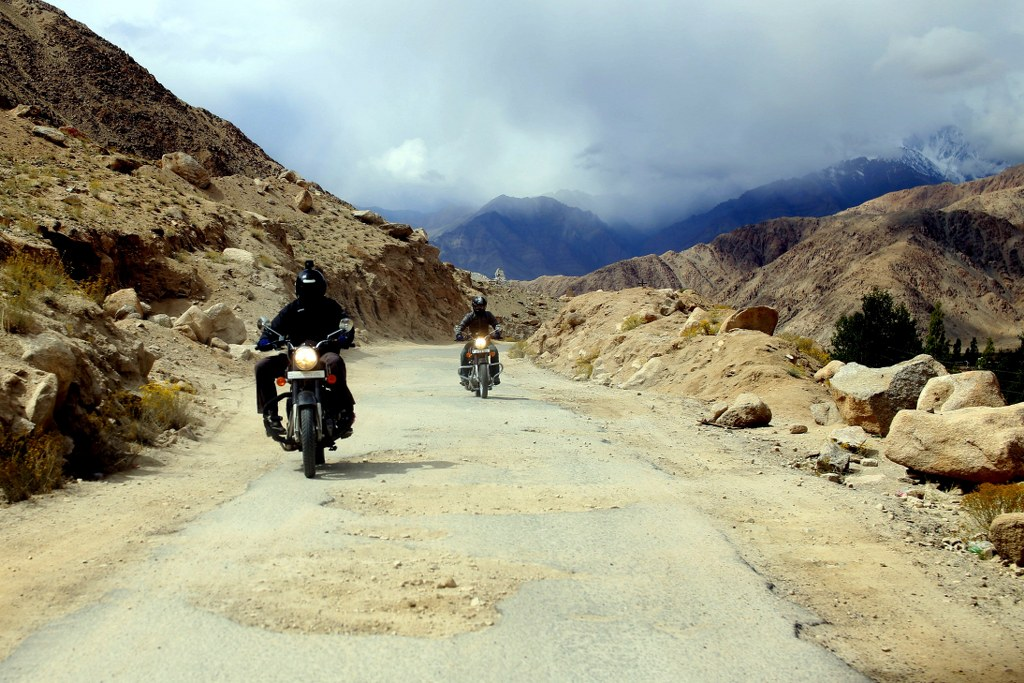 two_motorbikes_riding_on_a_dusty_mountain_road