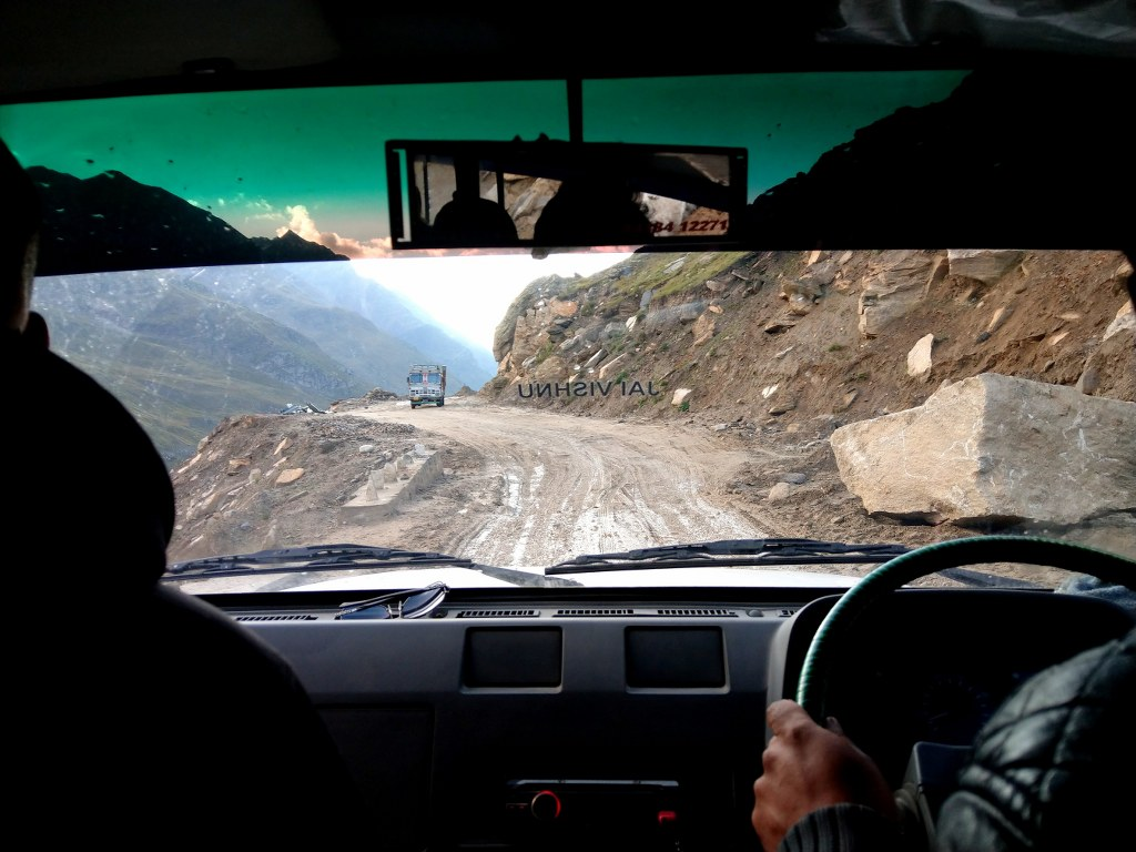 a_front_view_of_a_car_driving_through_the_himalayas