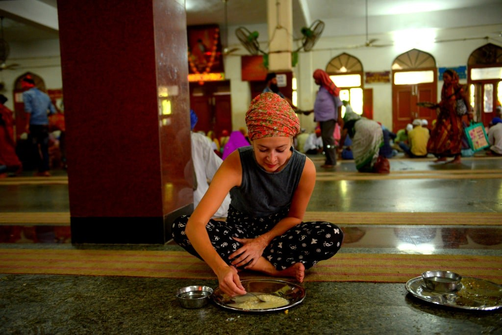 a_girl_with_covered_hair_sitiing_on_a_ground_and_eating_indian_food
