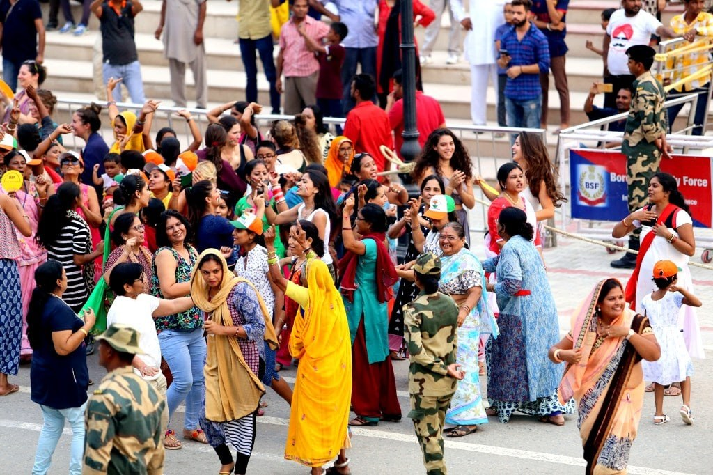 a_group_of_indian_women_dancing_in_colorful_saris
