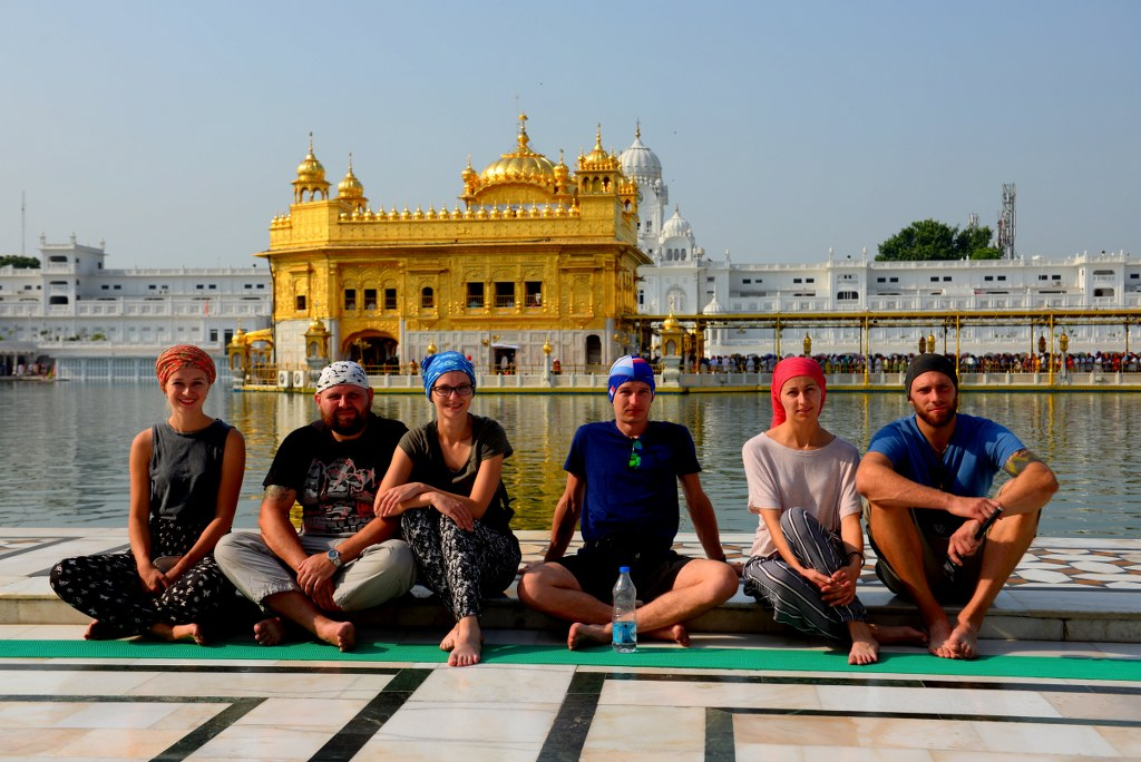 a_group_of_tourists_sitting_on_a_graound_in_front_of_the_golden_temple_in_amritsar