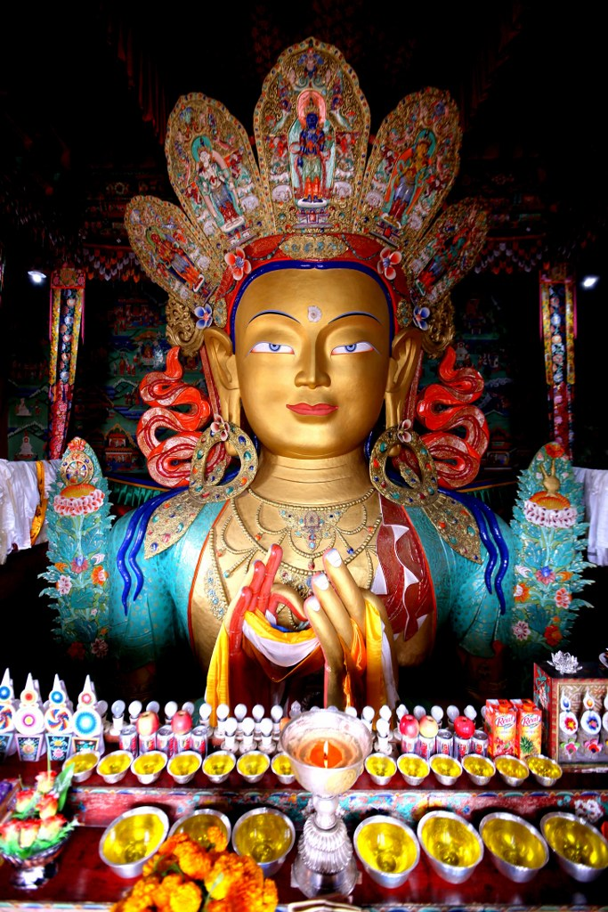 a_huge_colorful_buddha_sculpture_surrounded_by_gifts