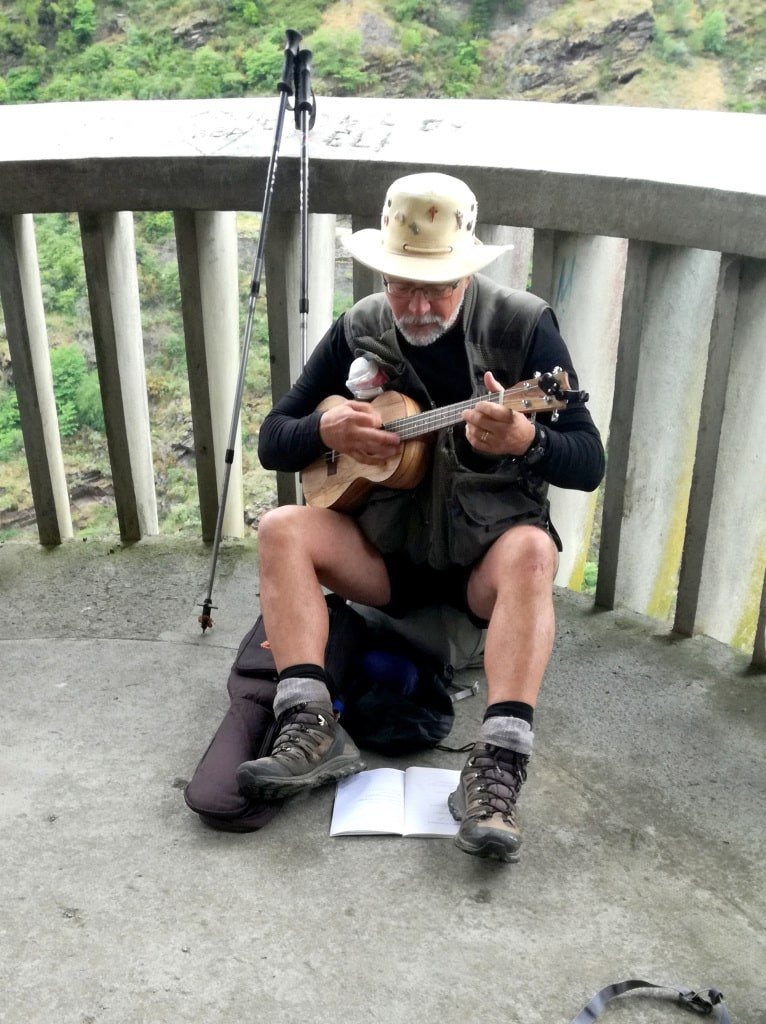 a_man_with_a_hat_on_his_head_sitting_on_a_ground_and_playing_on_the_little_guitar