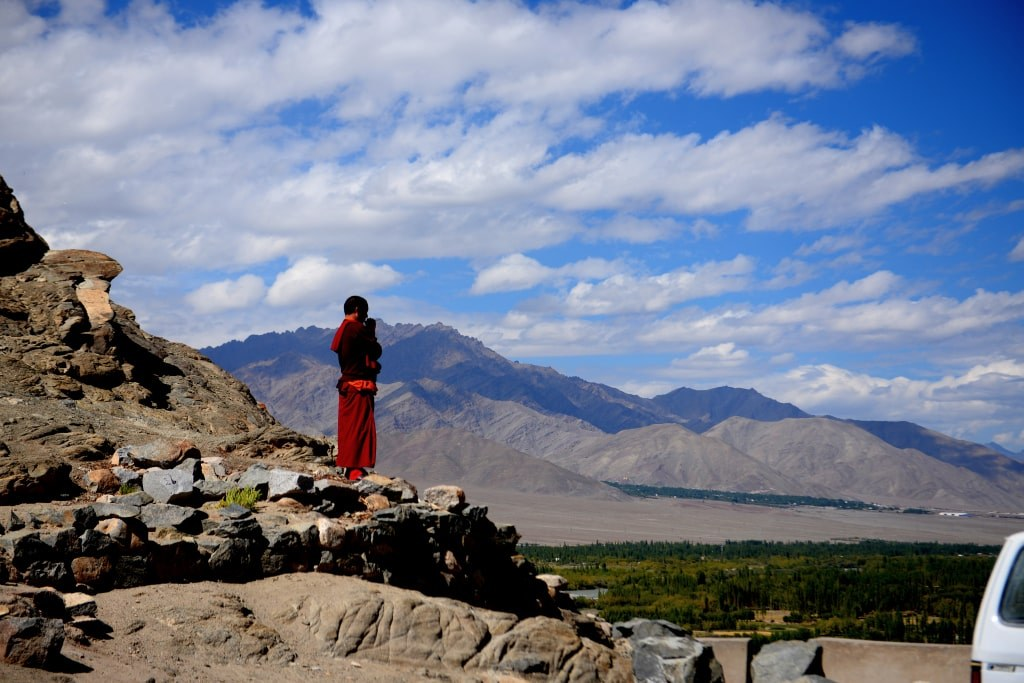 a_monk_in_a_red_robe_standing_on_the_edge_of_a_slope