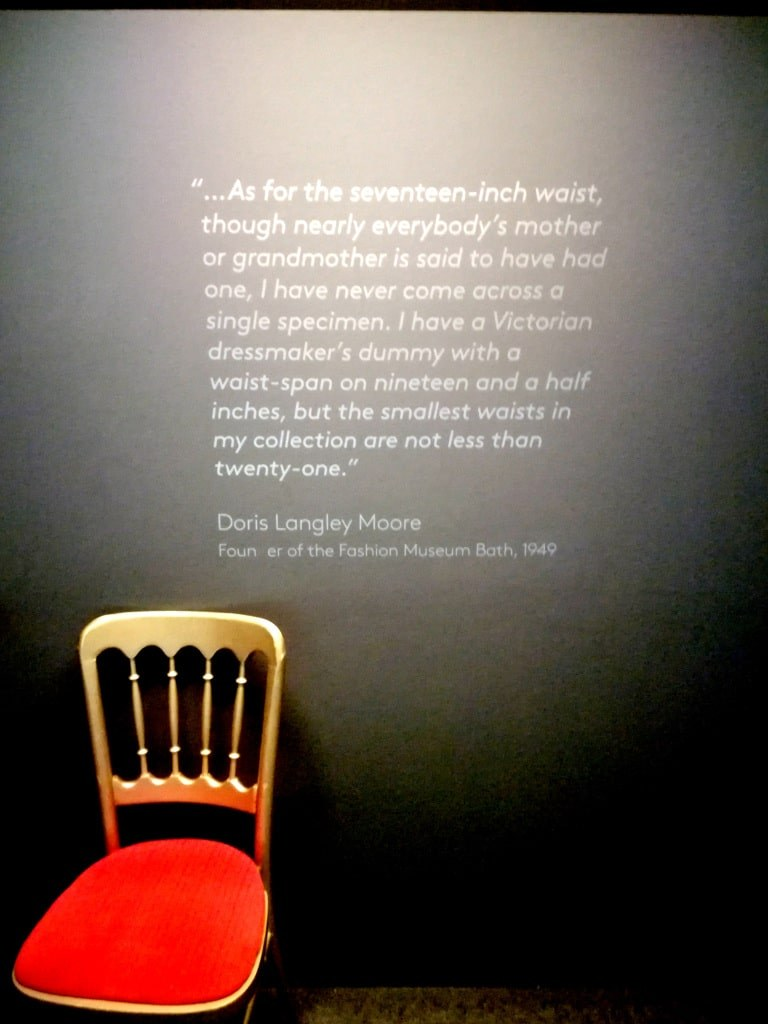a_red_chair_standing_in_front_of_a_wall_with_painted_sentences