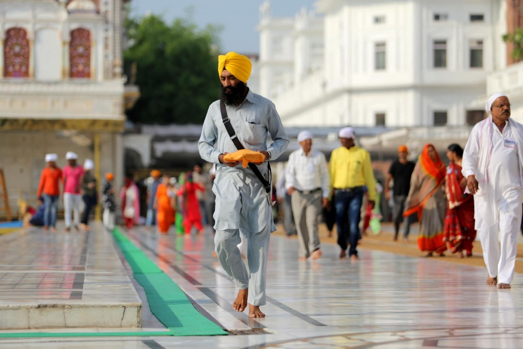 a_sikh_in_yellow_turban_Walking_on_a_golden_temple_square