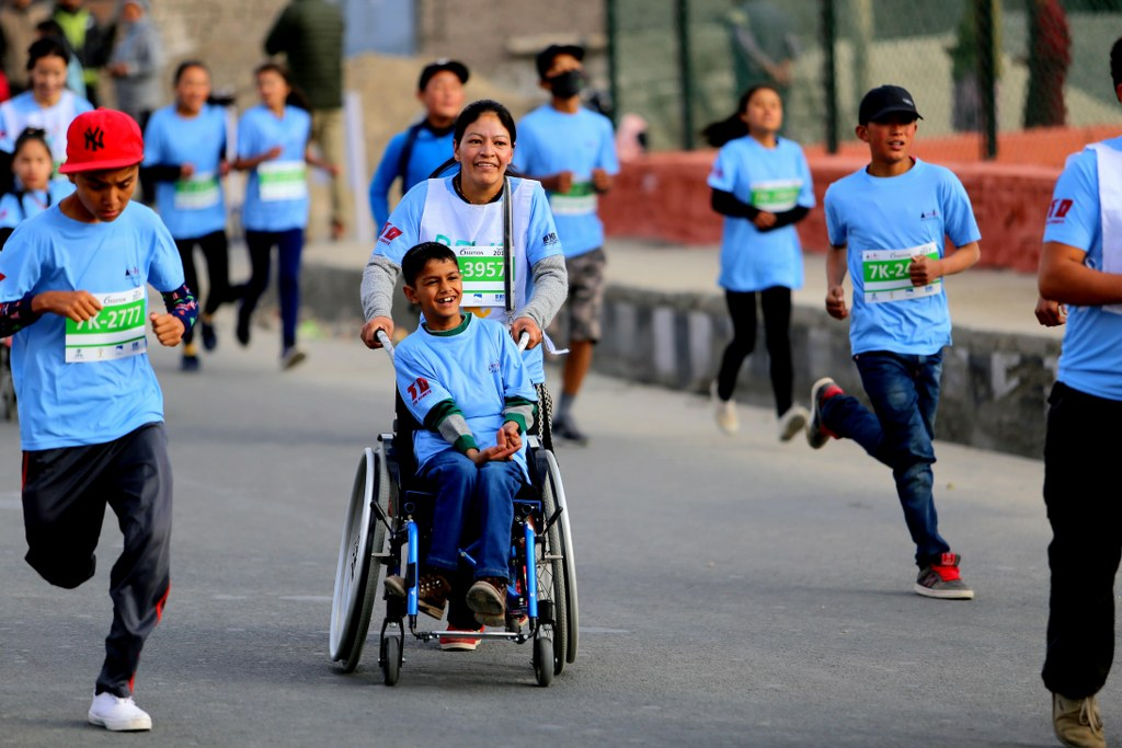 a_young_smiled_boy_in_a_wheelchair_taking_part_in_a_himalayan_marathon