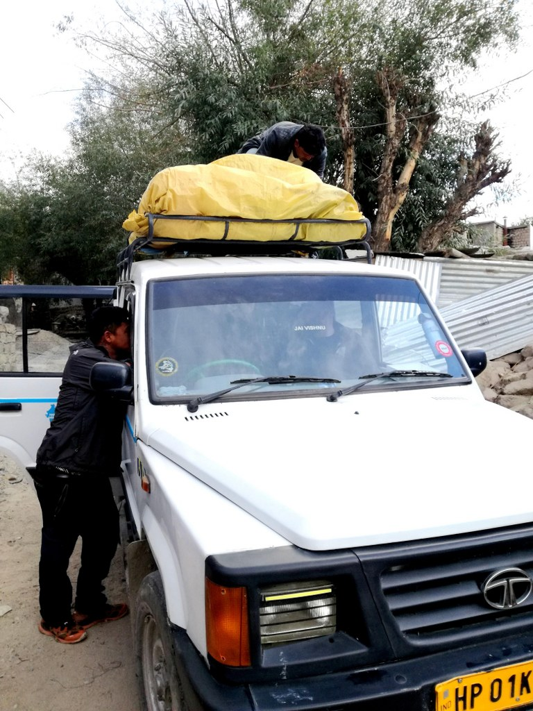 an_indian_men_attaching_bags_on_a_car_roof
