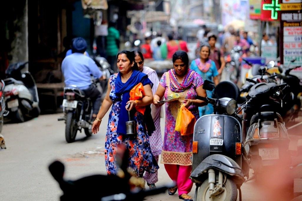 elegant_indian_women_in_colorful_saris_walking_on_a_street
