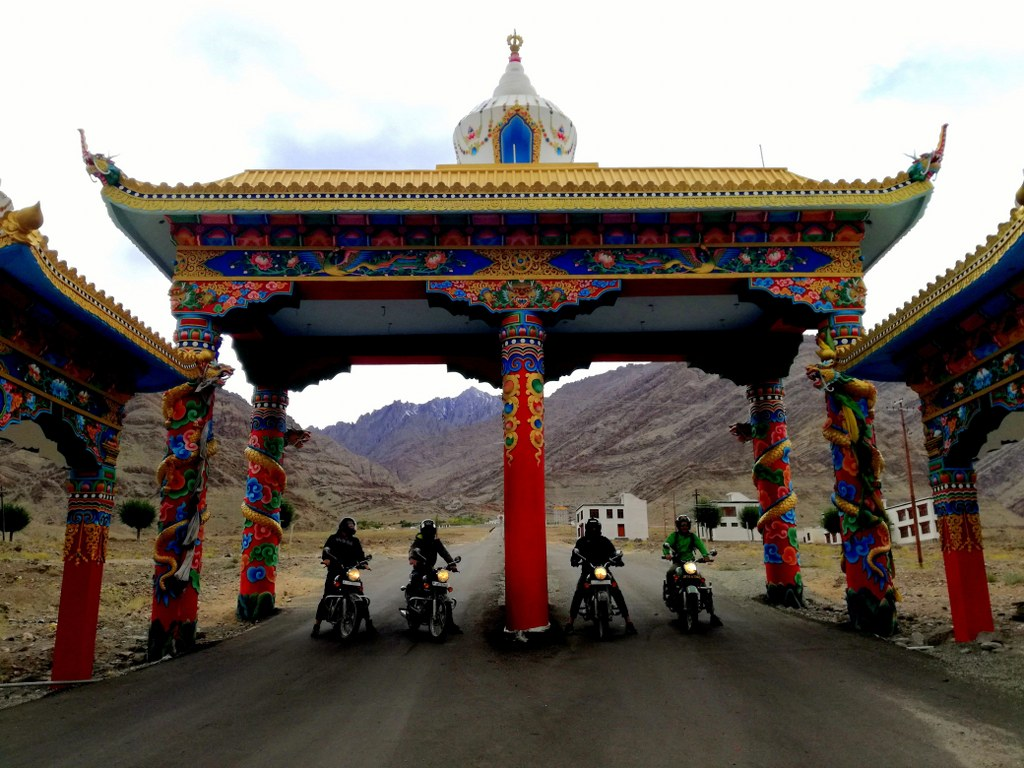 four_motorcyclists_on_their_motorbikes_standing_under_a_colorful_gate