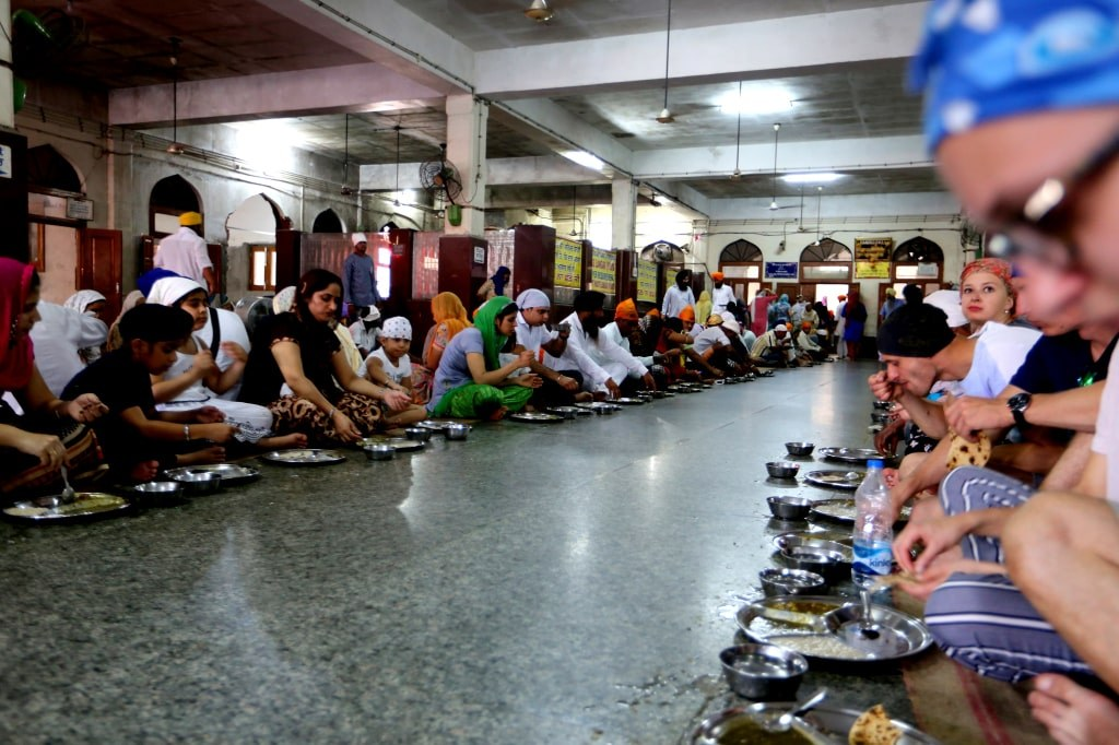 hundreds_of_people_sitting_on_a_ground_and_eating_breakfast