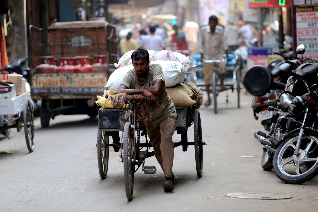 indian_men_pulling_heavy_trolley_attached_to_his_bike