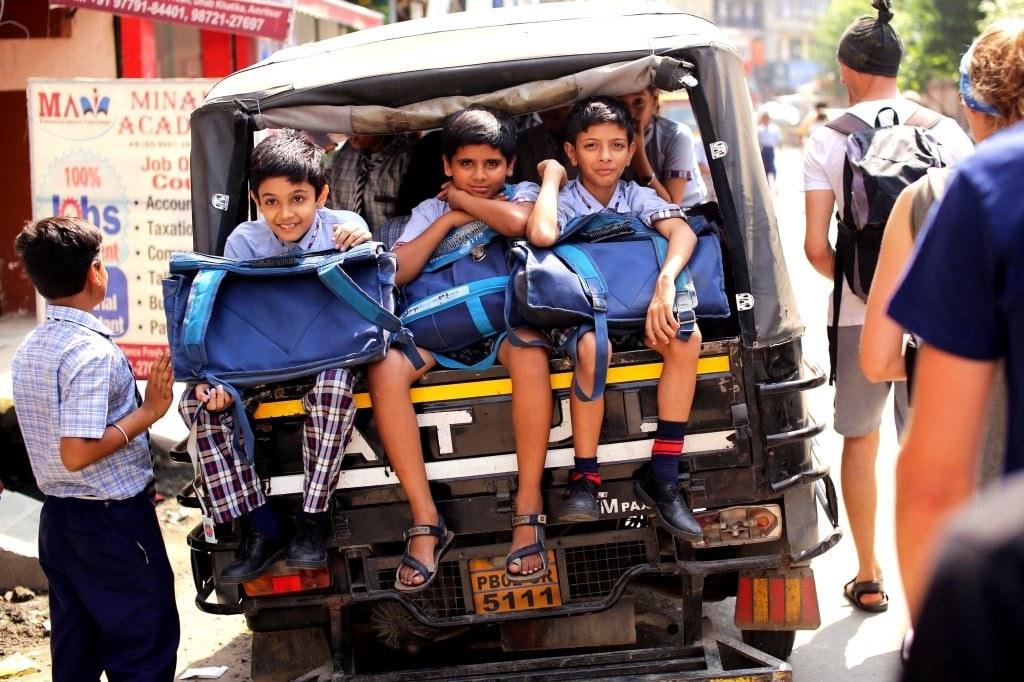 little_boys_in_school_uniforms_sitting_at_a_back_of_riksha