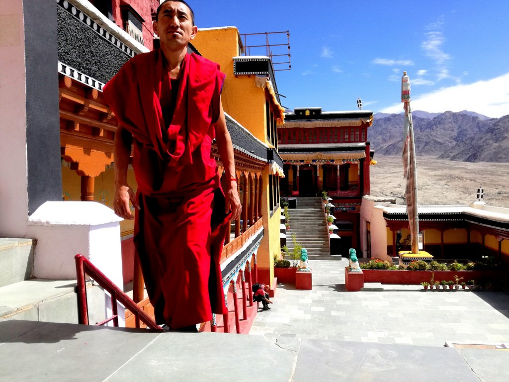 red_dressed_monk_climbing_a_high_stairway