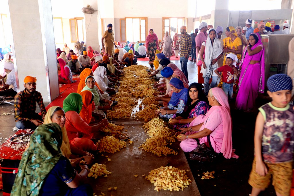 tens_of_indian_women_in_colorful_saris_sitting_on_a_flor_and_peeling_potatoes