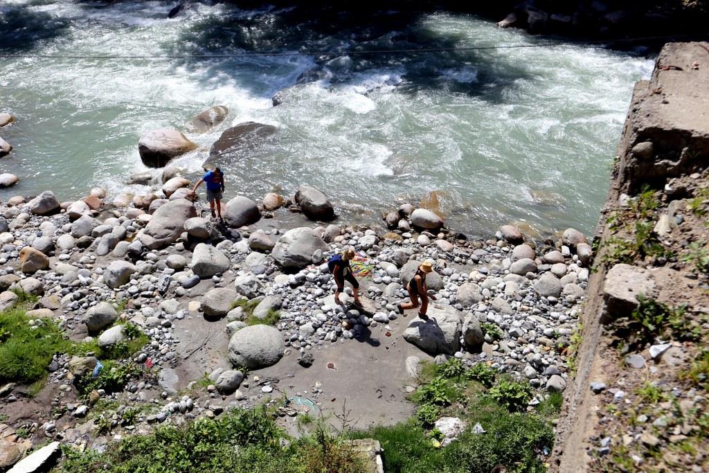 three_people_walking_on_a_rocky_riverside