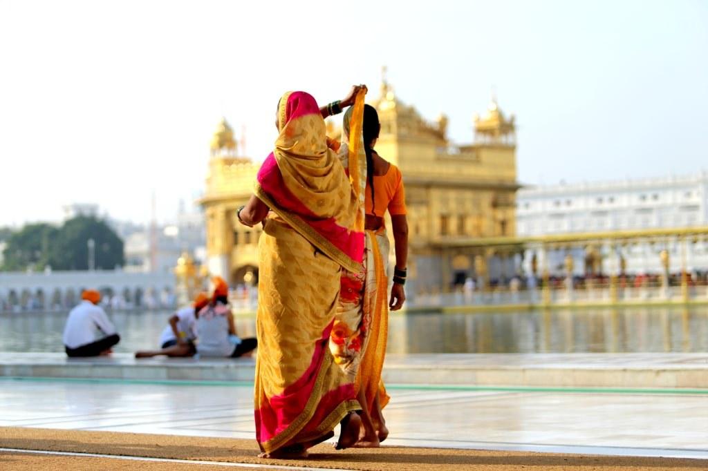 two_women_in_golden_seris_walking_outside_the_golden_temple_in_amritsar