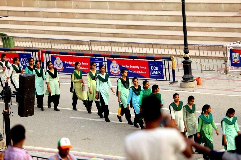 young_indian_girls_in_green_school_uniforms_Walking_to_take_sits