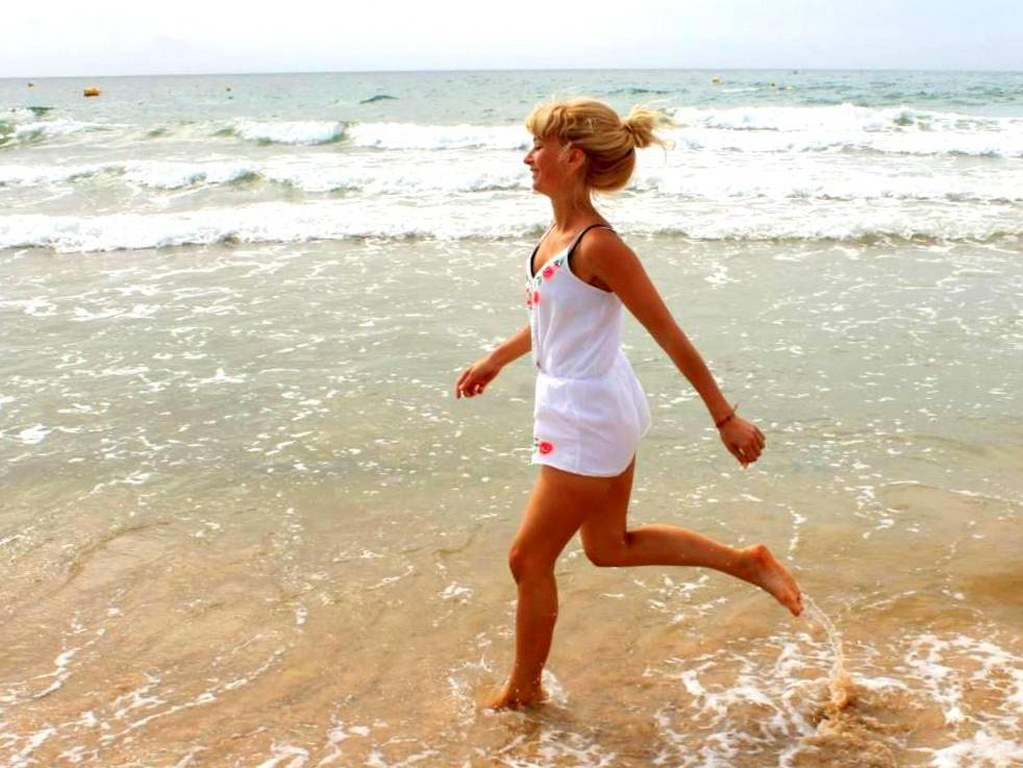 a_blond_girl_smiling_runs_on_a_waterfront