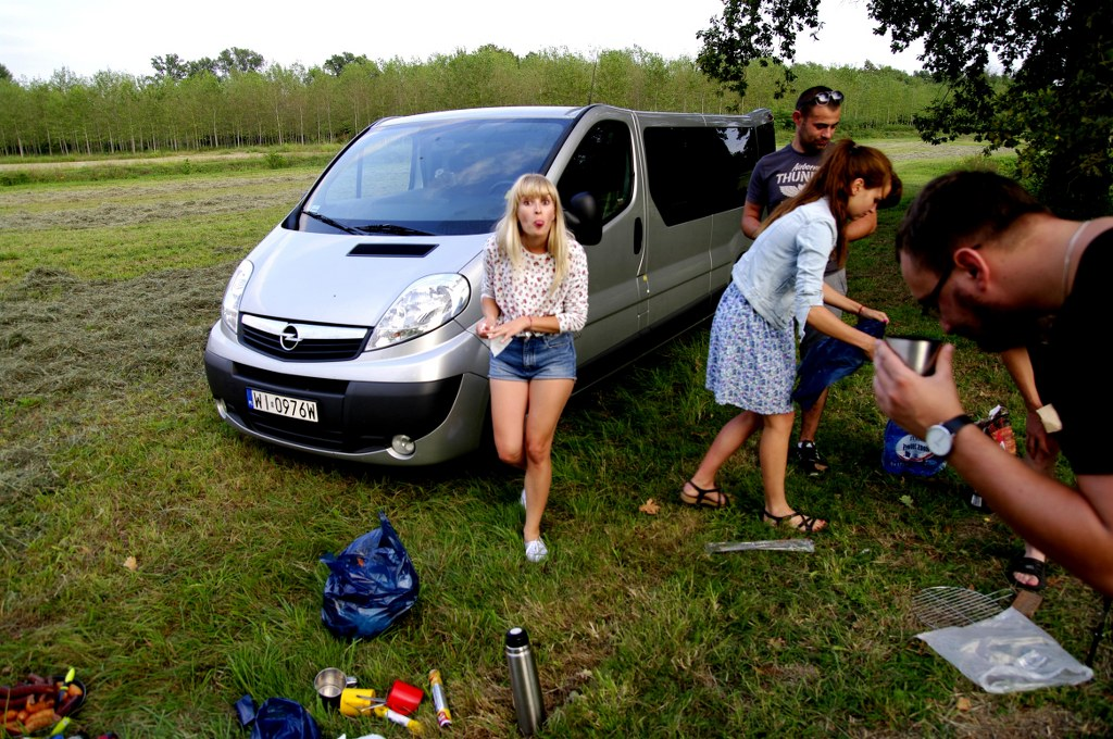 a_group_of_friends_preparing_a_barbecue_around_a_car