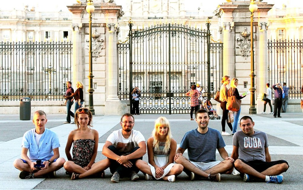 a_group_of_smiled_friends_sitting_on_a_ground_in_front_of_madrid_palace