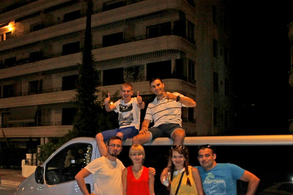 group_of_friends_sitting_on_a_minivan_roof