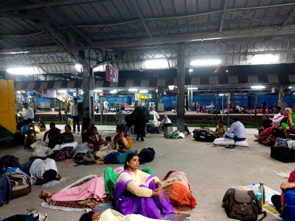 indian_people_sitting_on_a_ground_and_Waiting_for_a_train