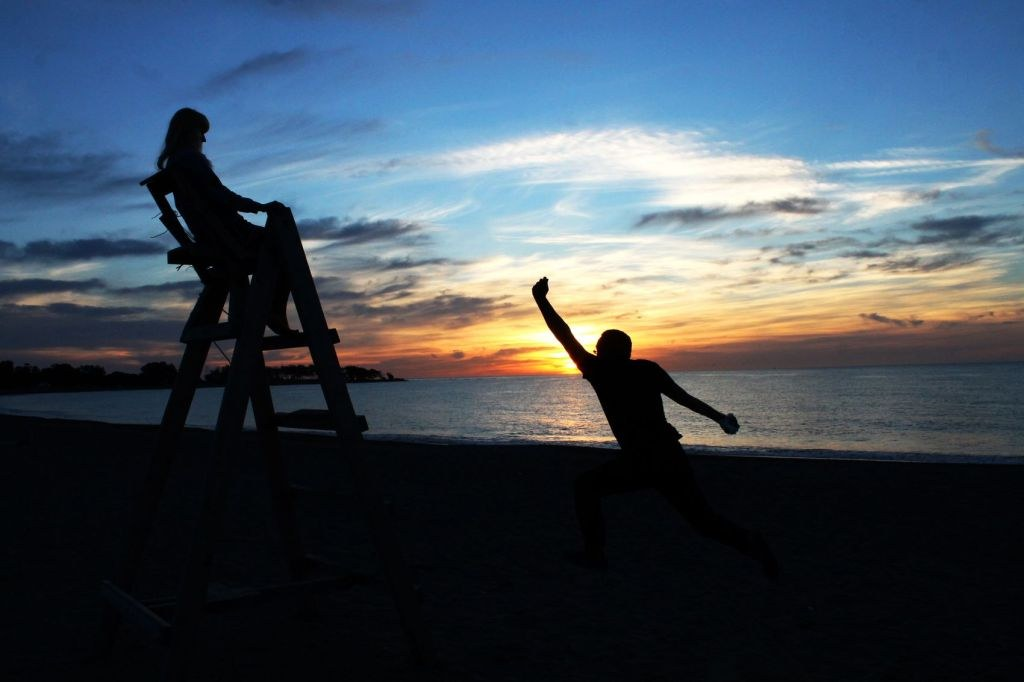 two_people_funny_possing_in_front_of_a_sunset