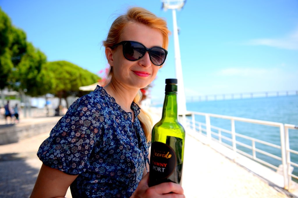 a_blonde_girl_sitting_under_sunshine_and_drinking_wine_in_porto