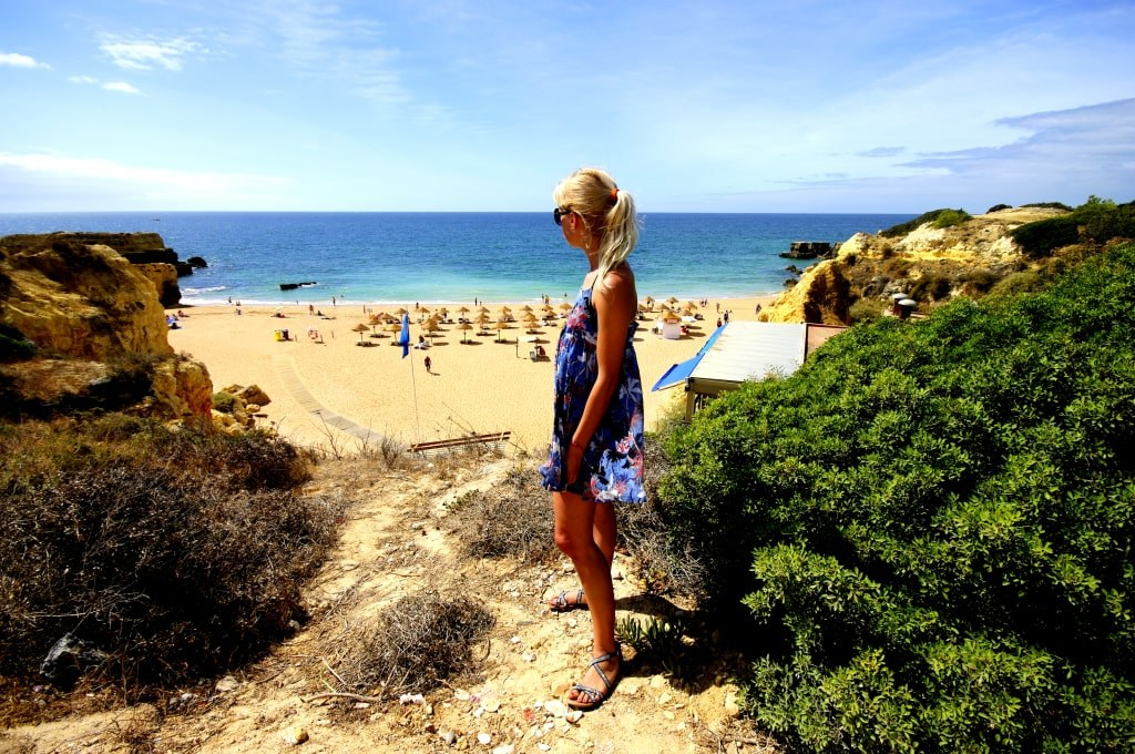 a_blonde_girl_standing_in_front_of_one_of_algarve_sandy_beaches