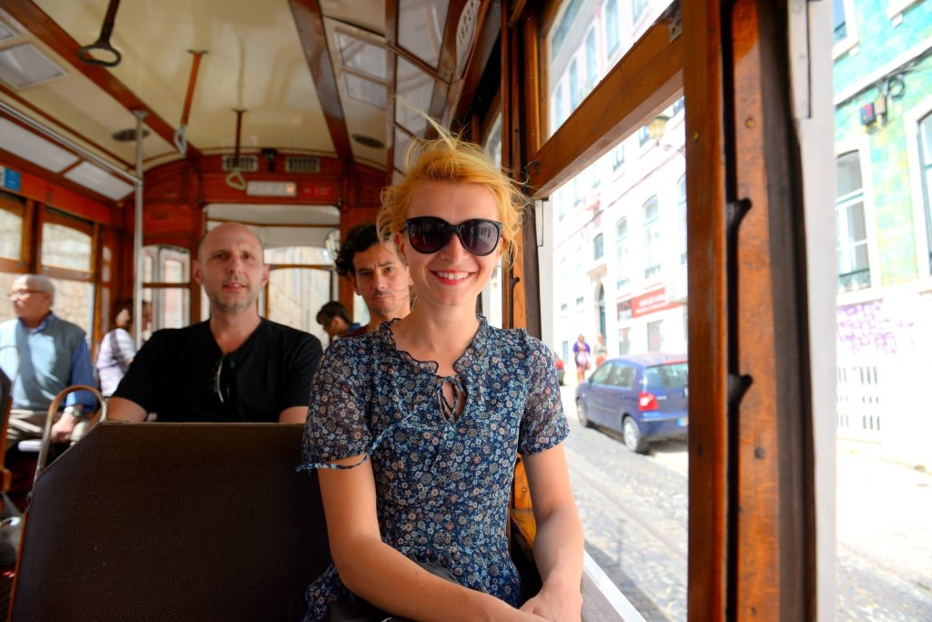 a_blonde_girl_travelling_by_a_famous_yellow_tram_in_lisboa