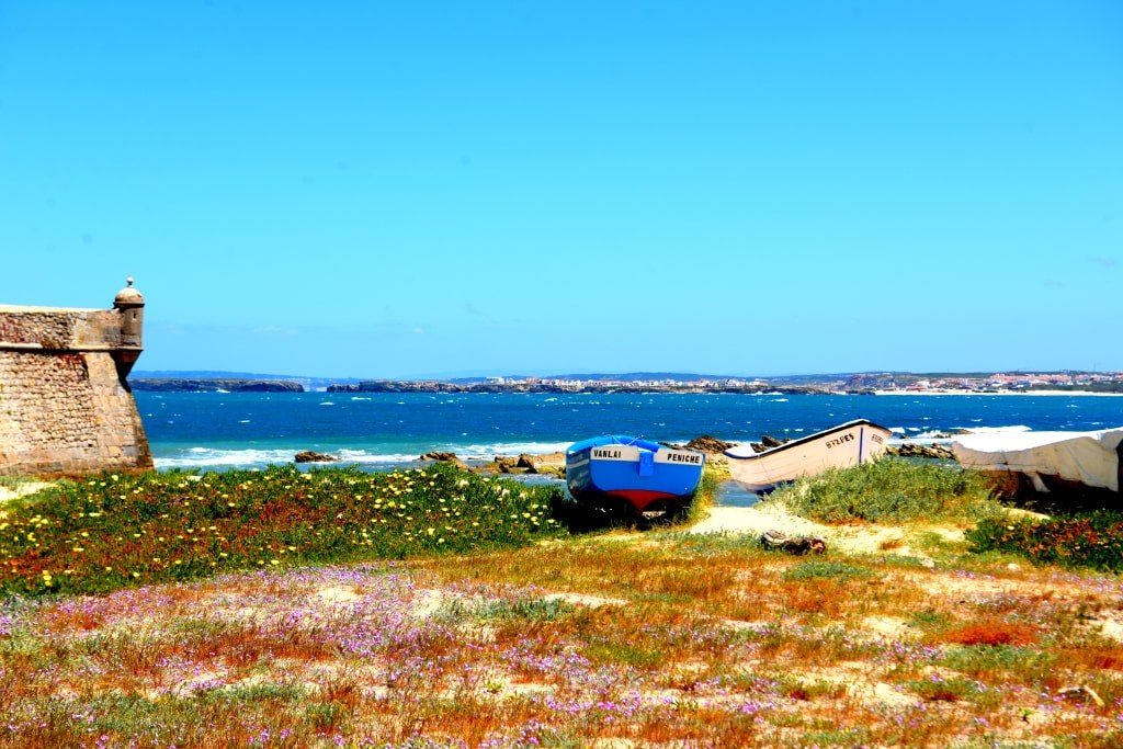 a_blue_boat_placed_on_a_sandy_coast_of_portugal