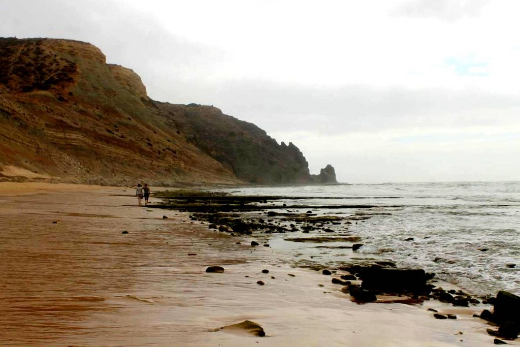 a_couple_Walking_on_a_wett_sandy_beach_in_portugal