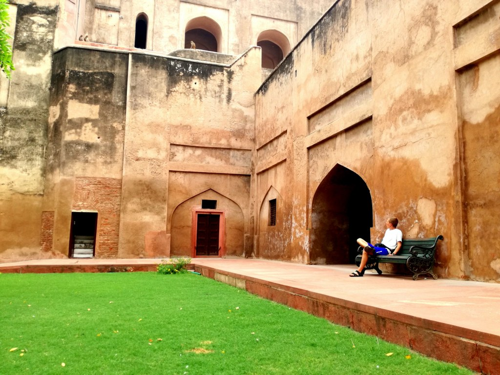 a_boy_sitting_on_a_bench_inside_the_red_fort_in_agra