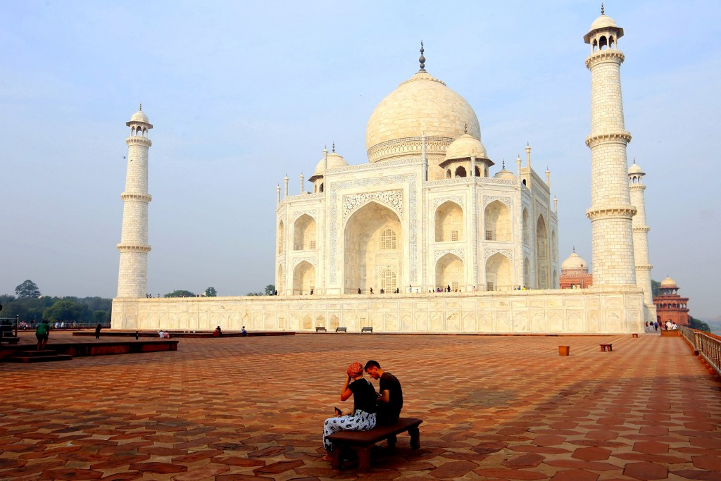 a_couple_sitting_on_a_bench_in_taj_mahal_surrounding