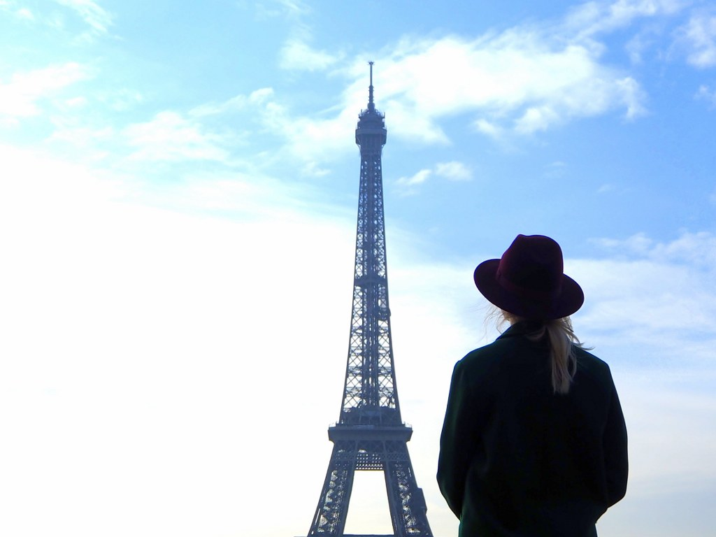 a_gilr_in_a_hat_standing_next_to_the_eiffel_tower