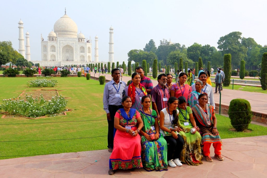 a_group_of_indian_people_in_colorful_clothes_sitting_on_a_bench_in_front_of_taj_mahal