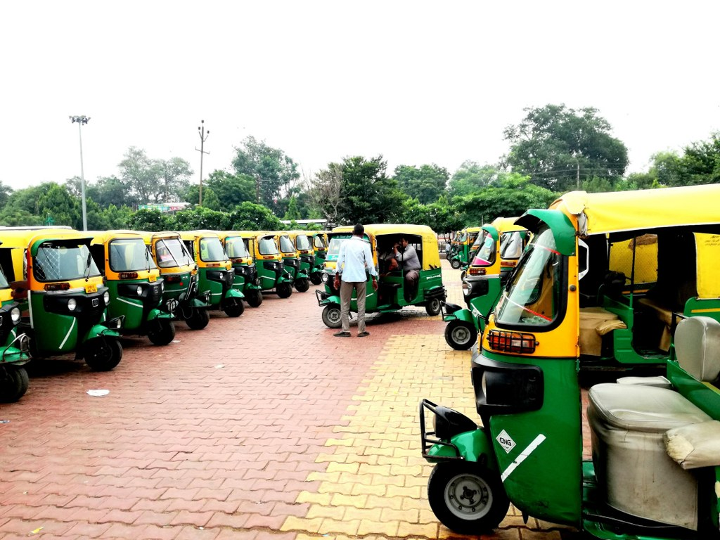 a_parking_space_with_tens_of_green_and_yellow_rikshas_in_agra