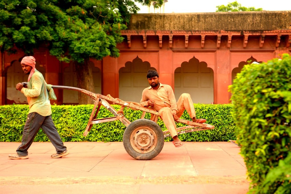 an_indian_guy_pulling_a_trolley_with_another_indiand_guy