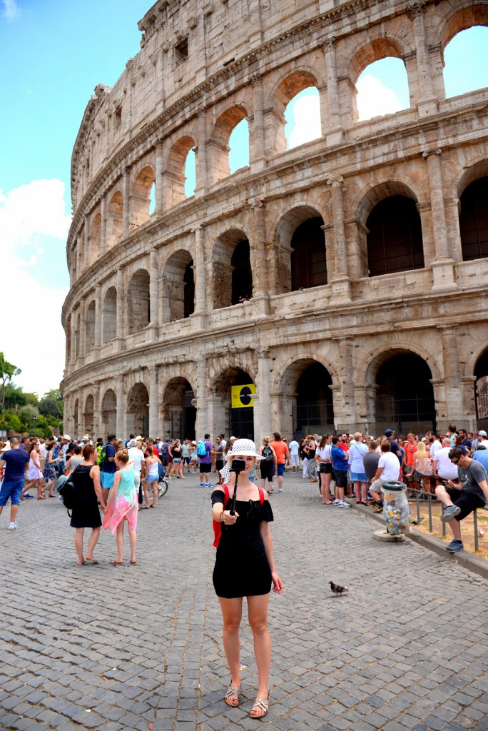a_blonde_girl_in_a_black_dress_standing_in_front_of_coloseum
