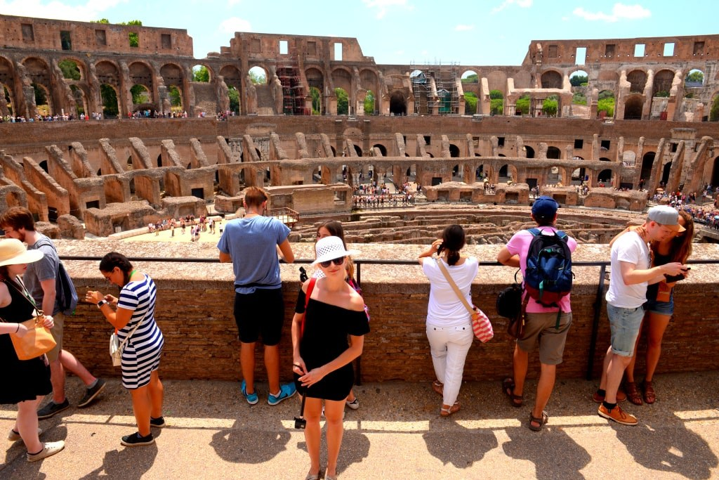 a_blonde_girl_in_a_white_hat_possing_to_a_photo_with_coloseum_behind_her