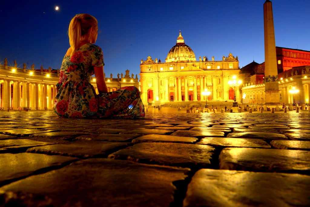 a_blonde_girl_sitting_on_a_ground_in_front_of_the_Saint_peters_basilica_in_vatican