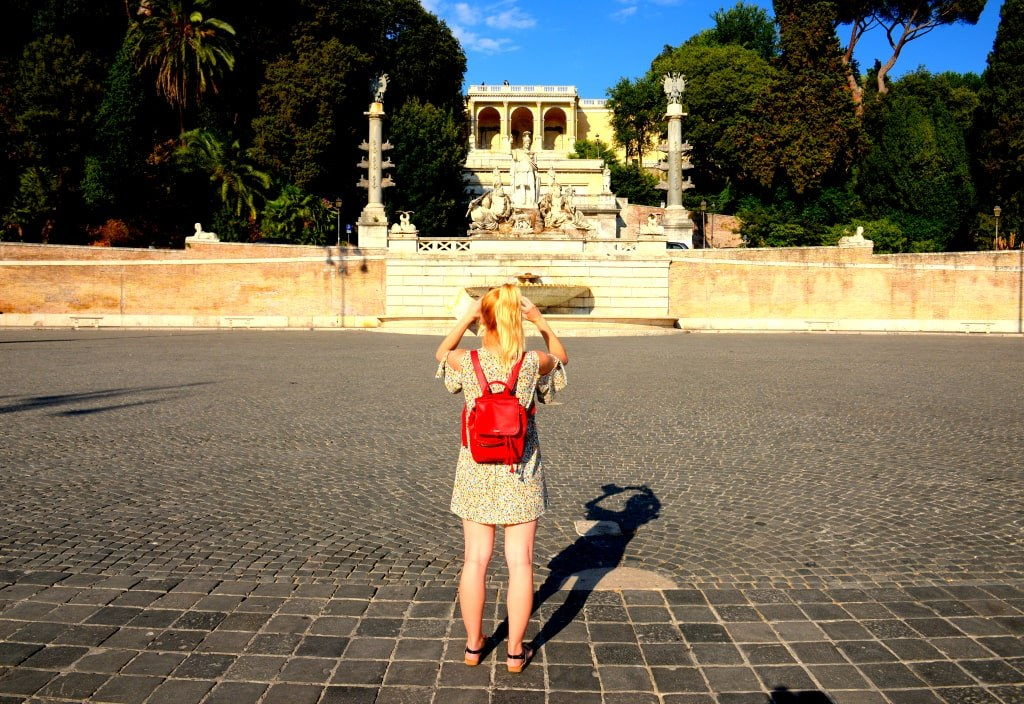 a_blonde_girl_with_a_red_backpack_taking_photos_on_a_street