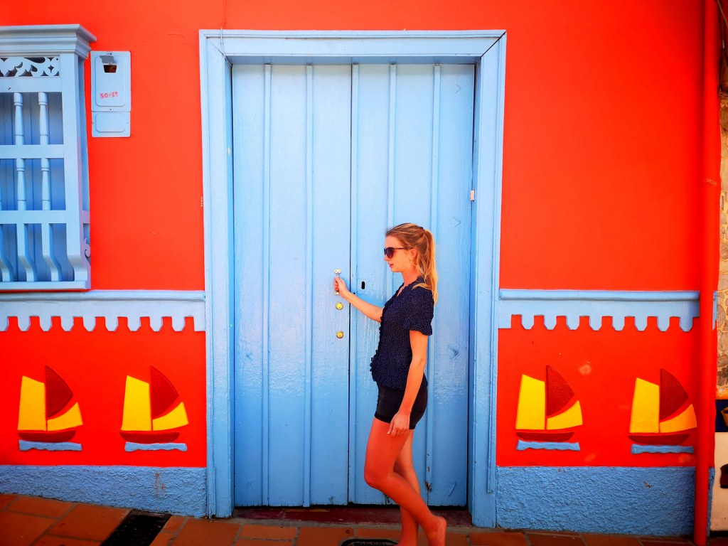 a_girl_standing_in_front_of_colorfully_painted_house