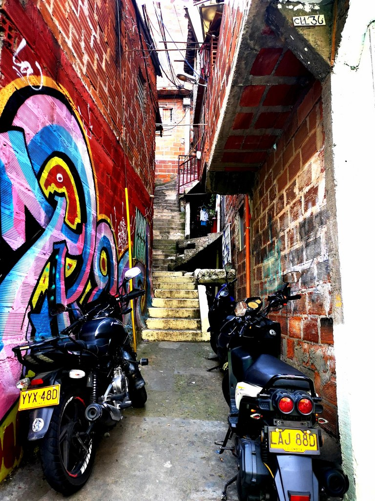 a_narrow_street_with_motorbikes_parked_and_colorfully_painted_walls