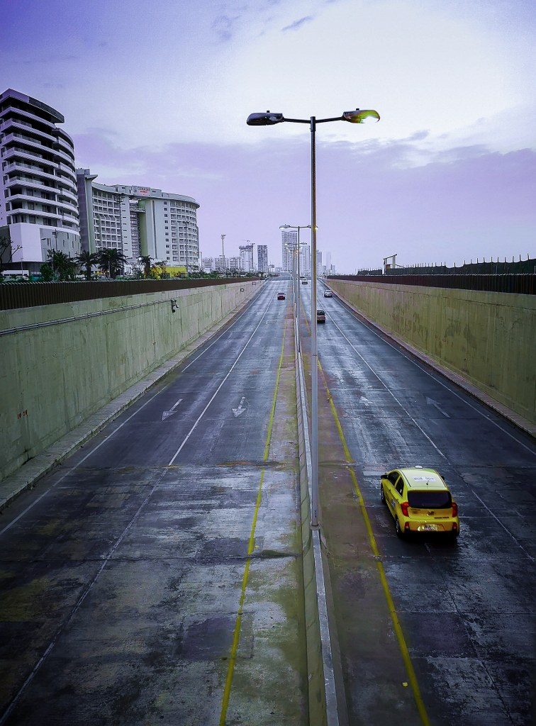 a_yellow_car_riding_an_empty_wide_road