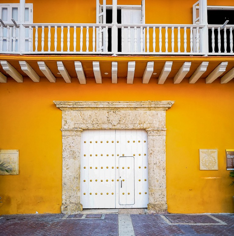 a_yellow_painted_bulding_with_a_white_balcony