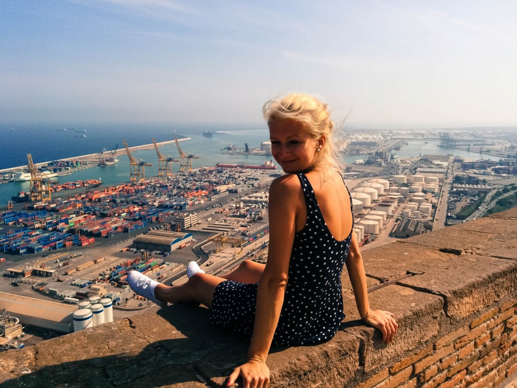 a_blond_gitl_sitting_on_an_edge_of_a_hill_with_a_panoramic_view_to_a_harbour_in_barcelona